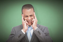 Composite image of stressed businessman putting his fingers on his temples Stock Photo