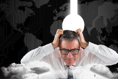 Composite image of stressed businessman touching his head Royalty Free Stock Photo