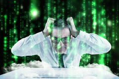 Composite image of stressed businessman using a keyboard Royalty Free Stock Image