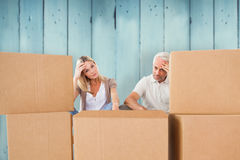 Composite image of stressed couple looking at moving boxes Royalty Free Stock Photography