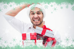 Composite image of stressed festive man holding gifts Stock Photography