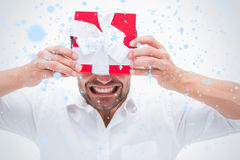 Composite image of stressed man holding a present Royalty Free Stock Image