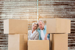 Composite image of stressed older couple with moving boxes Stock Images