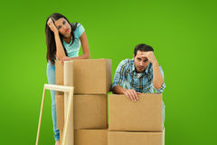 Composite image of stressed young couple with moving boxes Royalty Free Stock Photography
