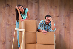 Composite image of stressed young couple with moving boxes Royalty Free Stock Image