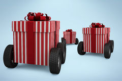 Composite image of striped red and white gift box on wheels Royalty Free Stock Photos