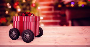 Composite image of striped white and red gift box with wheels Stock Images