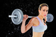 Composite image of strong female crossfitter lifting barbell behind head looking at camera Royalty Free Stock Images