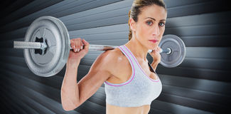 Composite image of strong female crossfitter lifting barbell behind head looking at camera Royalty Free Stock Photo