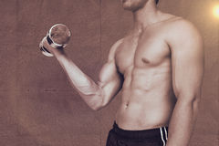 Composite image of strong man lifting dumbbell with no shirt on Stock Image