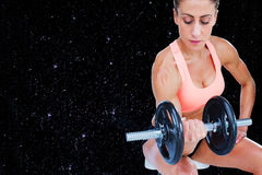 Composite image of strong woman doing bicep curl with large dumbbell. Strong woman doing bicep curl with large dumbbell against black background Royalty Free Stock Photography