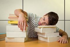 Composite image of student asleep in the library. Student asleep in the library against white tiling Royalty Free Stock Photography