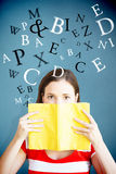 Composite image of student covering face with book in library Royalty Free Stock Photos