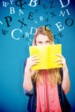 Composite image of student covering face with book in library Stock Photos