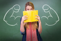 Composite image of student covering face with book in library Stock Images
