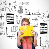 Composite image of student covering face with book in library Royalty Free Stock Images