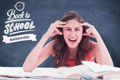 Composite image of student goes crazy doing her homework. Student goes crazy doing her homework against blue chalkboard Royalty Free Stock Images