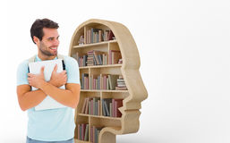 Composite image of student holding laptop. Student holding laptop against human face shape bookshelves stock photography