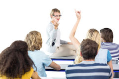 Composite image of student raising hand in classroom. Student raising hand in classroom against white background with vignette Stock Images