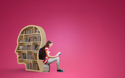 Composite image of student reading book in library. Student reading book in library against red vignette royalty free stock photography