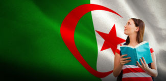 Composite image of student reading book in library. Student reading book in library against digitally generated algerian national flag Stock Photography
