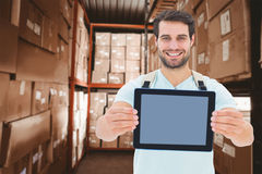 Composite image of student showing tablet. Student showing tablet against shelves with boxes in warehouse Royalty Free Stock Photos