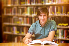 Composite image of student sitting in library reading Stock Image