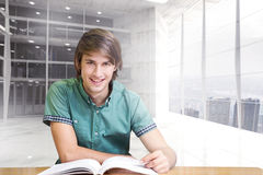 Composite image of student sitting in library reading Royalty Free Stock Photo