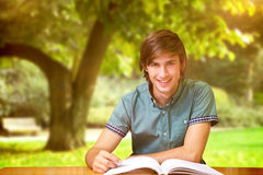 Composite image of student sitting in library reading Royalty Free Stock Image