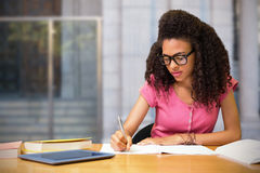 Composite image of student sitting in library writing Stock Photography