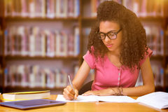 Composite image of student sitting in library writing. Student sitting in library writing against books on desk in library Stock Photo