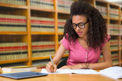 Composite image of student sitting in library writing Stock Images