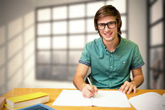 Composite image of student sitting in library writing Stock Image