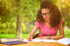 Composite image of student sitting in library writing Royalty Free Stock Photo