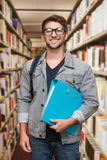 Composite image of student smiling at camera in library Stock Photography