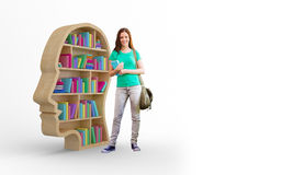 Composite image of student smiling at camera in library. Student smiling at camera in library against colorful books in human face bookshelves stock image