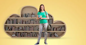 Composite image of student smiling at camera in library. Student smiling at camera in library against yellow vignette stock photos