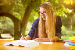 Composite image of student studying in the library Royalty Free Stock Images