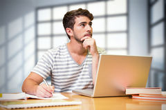 Composite image of student studying in the library with laptop. Student studying in the library with laptop against room with large windows showing city Royalty Free Stock Photos