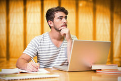 Composite image of student studying in the library with laptop Royalty Free Stock Photos