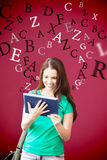 Composite image of student using her tablet in library Royalty Free Stock Image