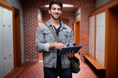 Composite image of student using tablet in library. Student using tablet in library against brick walled corridor with tiled flooring in college Stock Photo