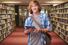 Composite image of student using tablet in library. Student using tablet in library against entrance of the college library Royalty Free Stock Photo