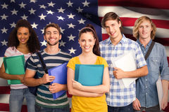 Composite image of students holding folders in college. Students holding folders in college against digitally generated american national flag Royalty Free Stock Images