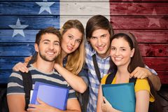 Composite image of students holding folders at college corridor. Students holding folders at college corridor against composite image of usa national flag Royalty Free Stock Photo