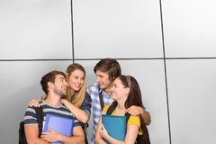 Composite image of students holding folders at college corridor. Students holding folders at college corridor against white tiling Royalty Free Stock Photo