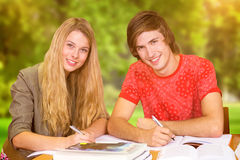 Composite image of students studying. Students studying against trees and meadow Royalty Free Stock Photography