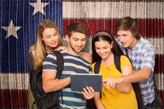 Composite image of students using digital tablet at college corridor. Students using digital tablet at college corridor against composite image of usa national Royalty Free Stock Photo
