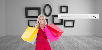 Composite image of stylish blonde in red dress holding shopping bags Stock Photo