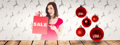 Composite image of stylish brunette in red dress showing sale bag Royalty Free Stock Photos